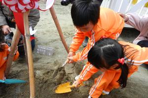 桜に土をかける子供たち